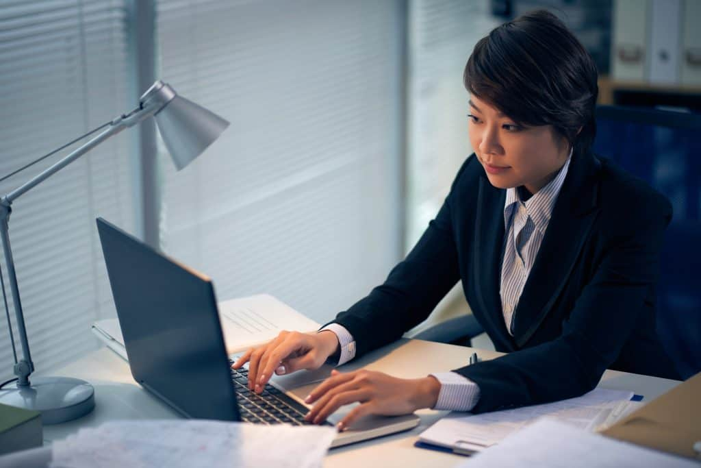 Female intern lawyer working on laptop in office